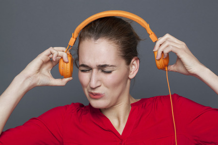 loud music: tinnitus headphones concept - stressed out 20s girl listening to loud music with earphones on,removing her earphones to avoid nightmare,studio shot Stock Photo
