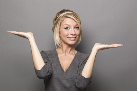 weighting: body language concept - smiling 20s blond woman weighting something on both palms of her hands for equal choice of product,studio shot on gray background
