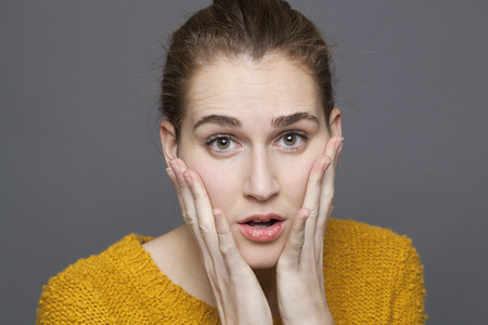 reassurance: doubt and confusion concept - portrait of surprised beautiful 20s girl expressing anxiety and distrust,studio shot on gray background Stock Photo