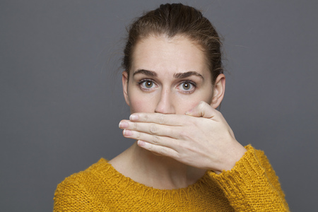negative feelings concept - portrait of surprised beautiful 20s girl covering her mouth for bad breath or taboo,studio shot on gray background