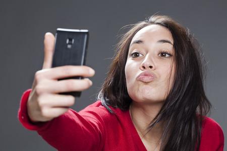 femme brune sexy: auto-portrait concept - 20s fille prenant son selfie dans l'envoi de baiser, fond gris en studio