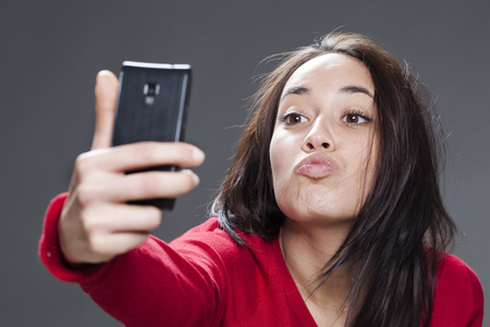 photo studio: self-portrait concept - 20s girl taking her selfie in sending kiss, grey background in studio