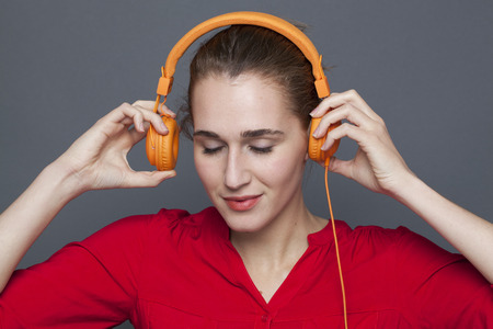 eyes closing: trendy headphones concept - peaceful 20s girl relaxing in listening to music with earphones on,closing her eyes to calm down,studio shot Stock Photo