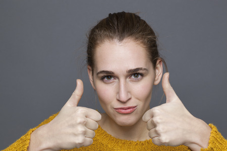 radiant approval concept - beautiful 20s girl pouting with two thumbs up for satisfaction and agreement,studio shot on gray background
