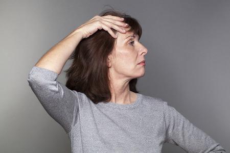arrogancia: orgullo y la arrogancia - mujer atractiva 50s orgullosos actuar con superioridad e infeliz indignados por la menopausia fondo, gris en el estudio Foto de archivo