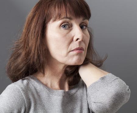 desconfianza: orgullo y la arrogancia - desilusionado hermosas 50s mujer que expresa la desconfianza y la tristeza, fondo gris en estudio Foto de archivo