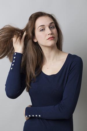 arrogancia: orgullo y la arrogancia - pretenciosa hermosa joven que juega con su pelo para la seducci�n y la insolencia, fondo gris en estudio