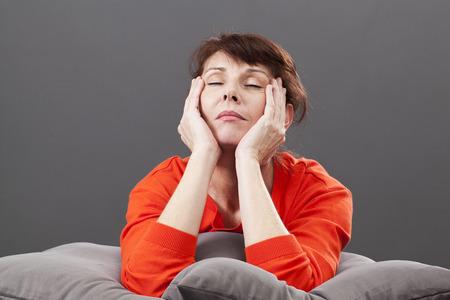 relaxamento: relaxamento zen - 50s cansados ??linda mulher meditar, relaxar para evitar ondas de calor, fechando os olhos encontram-se em confortáveis ??almofadas, estúdio fundo cinza
