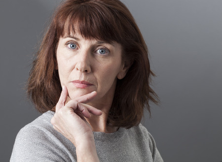 personas pensando: orgullo y la arrogancia - 50s infeliz mujer que expresa su tristeza, la sospecha y la nostalgia, fondo gris en estudio