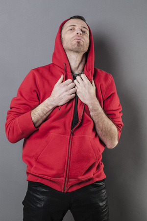 arrogance: pride and arrogance - outraged 40s man wearing a red hoodie acting offended for confrontation and attitude,gray background in studio Stock Photo
