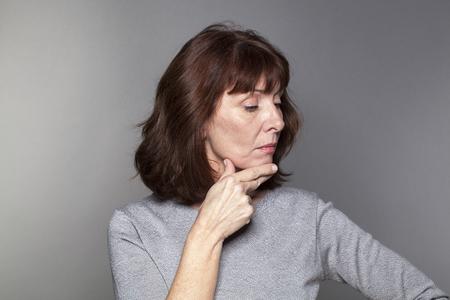 orgullo y la arrogancia - ofendido hermosa mujer madura que expresa tristeza y la depresión con el perfil orgullosos abajo, fondo gris en estudio Foto de archivo