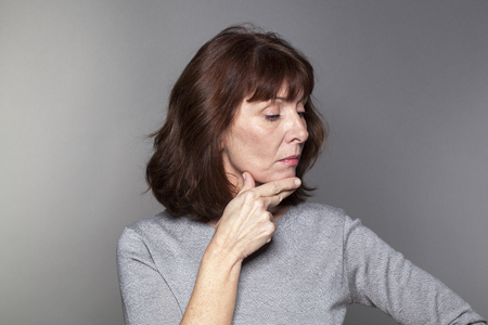 arrogance: pride and arrogance - offended beautiful mature woman expressing sadness and depression with proud profile down,gray background in studio