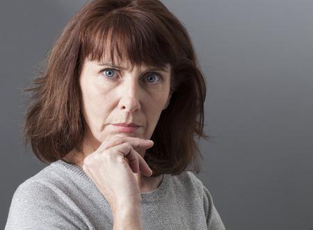 arrogancia: el orgullo y la arrogancia - disgustado mujer quej�ndose madura, expresando su desacuerdo e irritaci�n, fondo gris en estudio