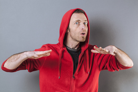 calming: zen relaxation - worried 40s man wearing red streetwear relaxing with soothing technique, hypnotizing with calming hand gesture, studio dark background