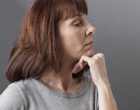 arrogancia: orgullo y la arrogancia - disgustado mujer de 50 a�os de mal humor, que expresa su desacuerdo y decepci�n, fondo gris en estudio