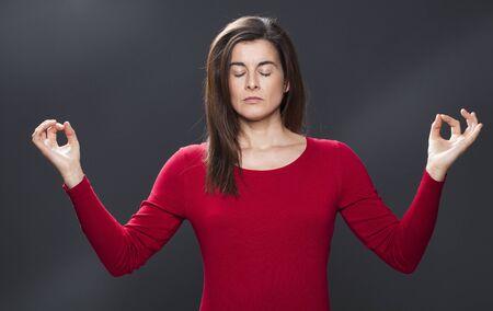 armonía: Zen de relajación - meditación 30s bella mujer se relaja con la técnica de yoga, la respiración para el bienestar y la armonía, estudio de fondo oscuro