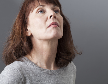 arrogancia: orgullo y la arrogancia - deprimidos mujer madura que expresa su desilusi�n, la nostalgia y la tristeza, fondo gris en estudio
