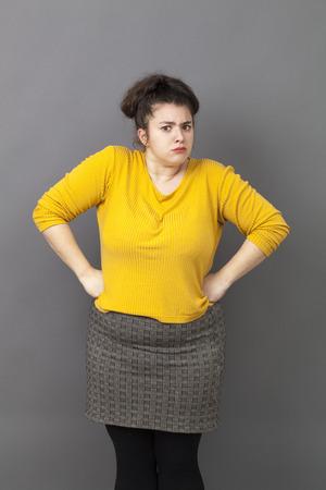 arrogancia: orgullo y la arrogancia - ofendidos gran mujer joven de pie con las manos en la cintura, exasperados por los cr�ticos, quej�ndose de expresar su actitud