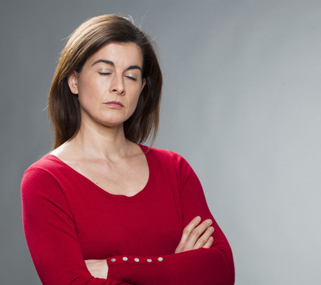 closing time: zen relaxation - overwhelmed 30s business woman closing her eyes, crossing arms for napping or meditating, taking time for wellbeing and harmony, studio gray background Stock Photo