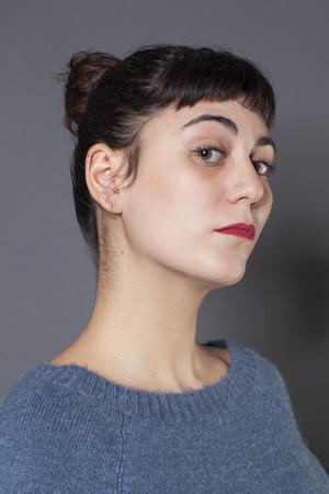 arrogancia: orgullo y la arrogancia - 20s orgullosos de la ni�a de piel clara que expresa su actitud con el perfil y la barbilla hacia arriba, fondo gris en el estudio