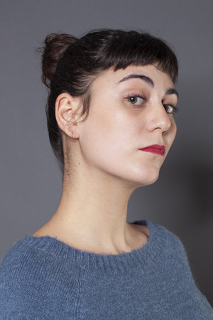 pretentious: pride and arrogance - proud 20s girl with fair skin expressing her attitude with profile and chin up,gray background in studio Stock Photo