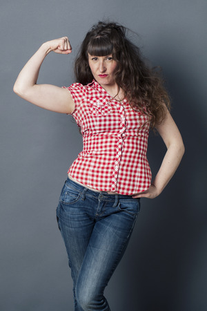 manlike: muscle concept - proud young woman with tomboy retro look raising her arm to enjoy female power, symbol of freedom,studio shot Stock Photo