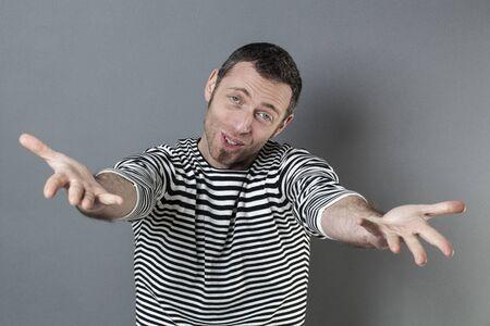 grabbing: hand gesture concept - generous 40s man grabbing or presenting something in empty hands forwards,studio shot