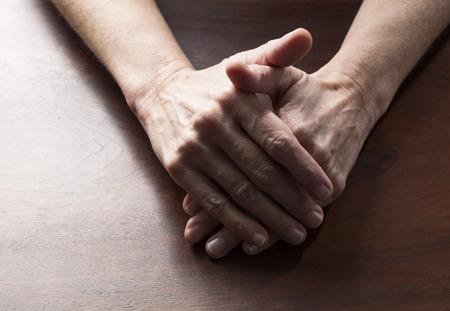 paciencia: hablando concepto de las manos - las manos femeninas se unieron para la confusión o la paciencia en la mesa de madera, tiro del estudio Foto de archivo
