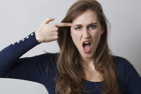 outraged: despair and humor concept - shouting young woman pretending killing herself,loosing temper with finger pointing to her temple,studio shot