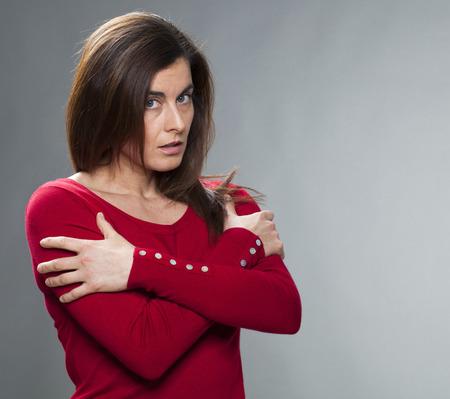Schutzkonzept - beleidigt 30s Frau mit den Armen für Unsicherheit und Enttäuschung, Studioaufnahme gefaltet stehen