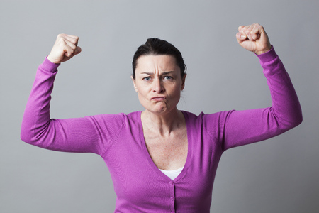 tied hair: muscle concept - enraged 40s woman gesturing with arms raised showing her rebellion and anger,studio shot Stock Photo