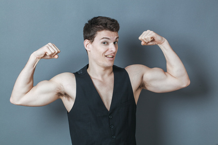cartoon body: muscle concept - playful young man flexing his muscles showing his strength and male power,studio shot,low contrast effect Stock Photo