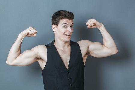 spier concept - speelse jonge man buigen zijn spieren toont zijn kracht en mannelijke macht, studio-opname, een laag contrast effect