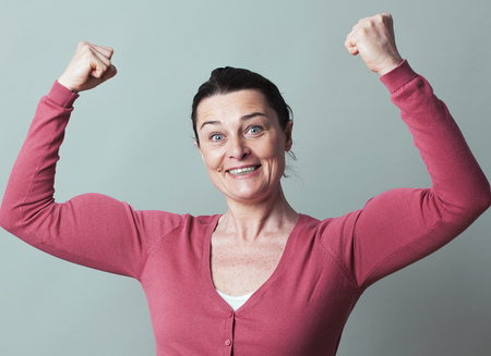 manlike: muscle concept - joyous beautiful 40s woman flexing her muscles up for metaphor of female success and power,studio shot, low contrast effect Stock Photo