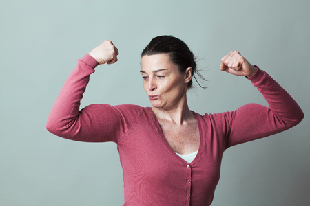 muscle concept - proud beautiful 40s woman admiring her flexing muscles for metaphor of female strength and power,studio shot, low contrast effect