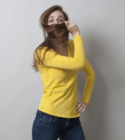 dubious: protection concept - proud young woman standing in covering her mouth with her hair for fun shyness,studio shot