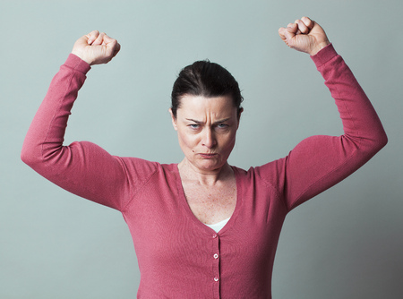 arrogancia: concepto muscular - 40s indignados mujer levantando sus m�sculos para la met�fora de la libertad y el poder femeninos, tiro del estudio, el efecto de bajo contraste