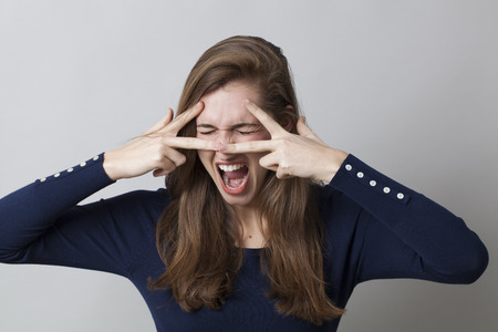 screaming face: excitement and humor concept - shouting young woman making a pulp fiction v-sign mask expressing anger and frustration,studio shot Stock Photo