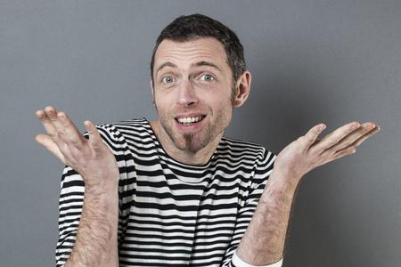 negligence: negligence concept - happy 40s man expressing carefree responsibility for childish mistake,studio shot