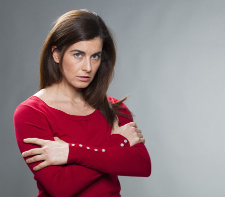 thirties: protection concept - suspecting 30s woman standing with arms crossed for insecurity and comfort,studio shot