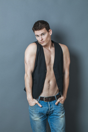 bare chest: muscle concept - embarrassed young man putting his big muscular arms in his jeans pockets to hide his muscles and bare chest,studio shot,low contrast effect Stock Photo