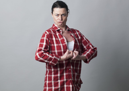butch: muscle concept - strong 40s woman with fists tight together sticking out chest showing her courage,studio shot
