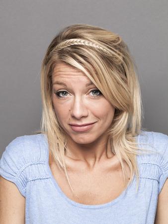 careless: negligence concept - coward young blond woman expressing careless arrogance for mistake,studio shot