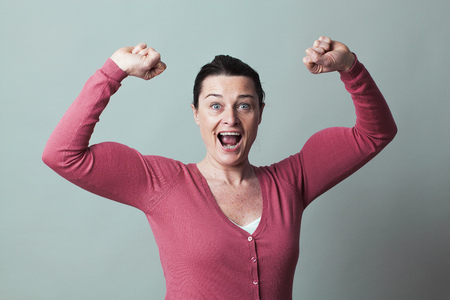 40s: muscle concept - laughing beautiful 40s woman proud of flexing her big muscles for metaphor of success and female power,studio shot, low contrast effect Stock Photo