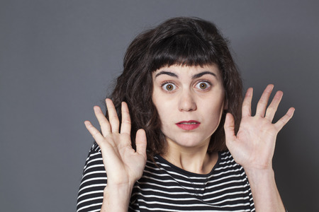 eyes wide open: negligence concept - terrified young brunette woman expressing fear with eyes wide open for mistake,studio shot Stock Photo