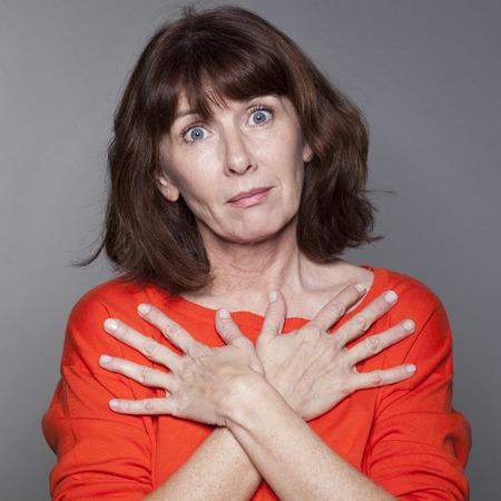 mujer decepcionada: concepto de protecci�n - hermosa mujer madura disgustado con las manos sobre el pecho para la comodidad y el dolor, tiro del estudio