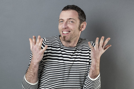 40s: hand gesture concept - happy extrovert 40s man expressing himself with hands talking,studio shot