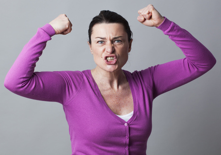 exasperation: muscle concept - furious 40s woman gesturing with arms raised showing her exasperation and frustration,studio shot Stock Photo