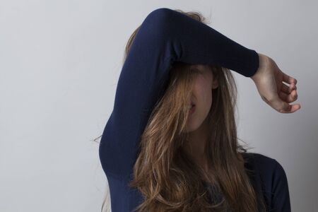 haircare concept - beautiful young woman hiding her face with her hair and arm for beauty regret,studio shot