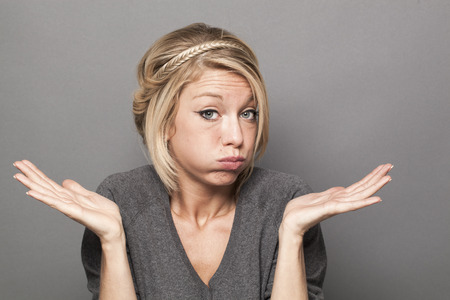 reproach: negligence concept - bored young blond woman blowing her cheeks out with careless hand gesture,studio shot Stock Photo